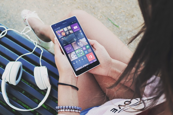 une fille tenant un smartphone Windows phone